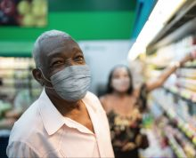Portrait of senior man with face mask shopping at supermarket